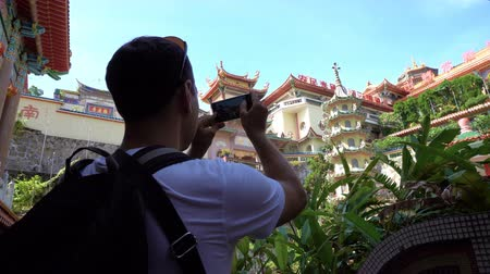 Caucasian man taking photo of Chinese temple