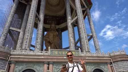 Young caucasian man taking selfie with Guan Yin statue Vídeos