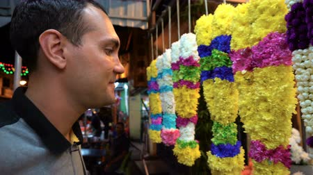 Caucasian man smelling Indian religous flower necklace at market stall Vídeos