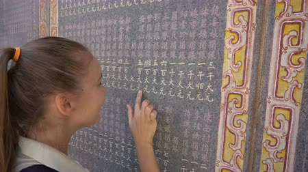 Female tourist look at chinese inscription on temple wall