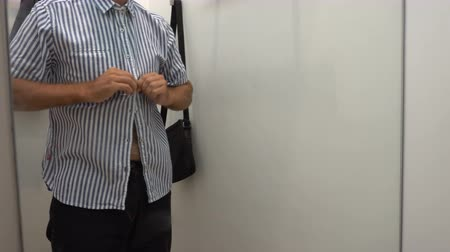 Caucasian man trying shirt in fitting room. Shopping Vídeos