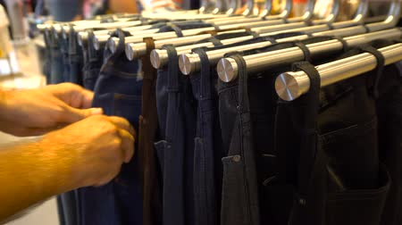 Male customer choosing jeans at shopping mall
