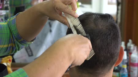 Female barber cut hair of caucasian man in Asian barbershop Vídeos