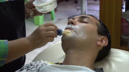 shaving foam : Female barber shaving caucasian man in Asian barbershop