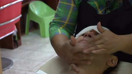 taberna : Female barber putting lotion after shaving of caucasian man in Asian barbershop Stock Footage