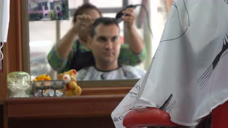 Female barber cut hair of caucasian man in Asian barbershop. Mirror reflection