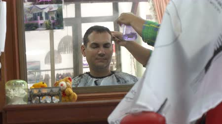 Barber spraying caucasian man hair in Asian barbershop. Mirror reflection