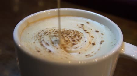 Stirring a cup of coffee cappuccino, slow motion, close up Vídeos