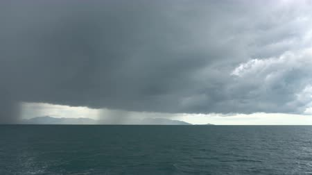 Floating away from storm. Rain in the distance over sea