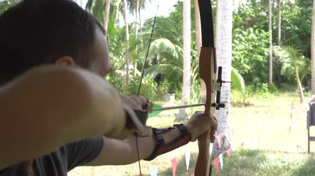 Caucasian man shooting with bow at archery