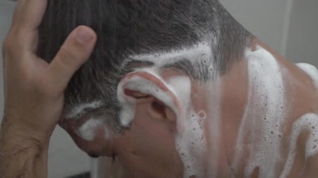 Caucasian man wash head with shampoo Stock Footage