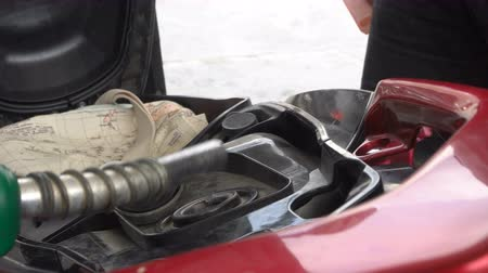 tankowanie : Close-up of a male hand using a petrol pump to fill scooter up with fuel