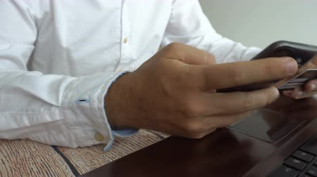 utilidade : Man paying online inserting credit card number on mobile phone. Internet banking