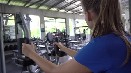 construção muscular : Young woman building triceps and biceps at gym