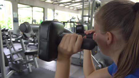 мышечной построить : Young woman building triceps and biceps at gym