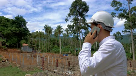 gadjet : Engineer talking on mobile phone at construction site Stock Footage