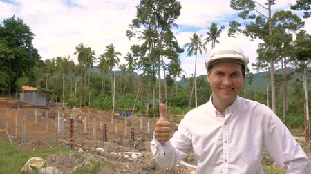 usta : Portrait of smiling happy successfull engineer thumbs up at construction site