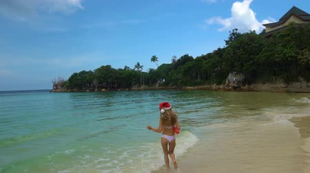 вводить : Young Woman in Santa Claus Hat Run into the Sea. Celebrating New Year in hot country Стоковые видеозаписи