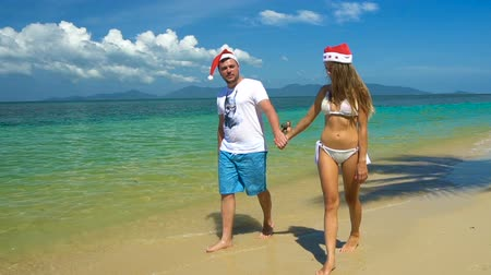 романтика : Romantic Couple Walk along the Beach in Santa Claus Hats. Celebrating New Year in hot country
