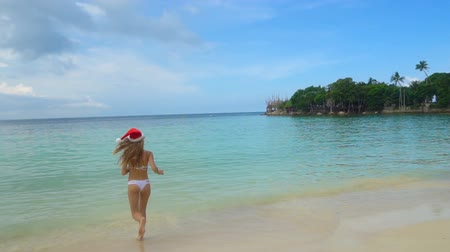 入る : Young Woman in Santa Claus Hat Run into the Sea. Celebrating New Year in hot country 動画素材