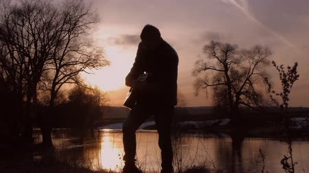 spaniard : The man playing the guitar at sunset (silhouette)
