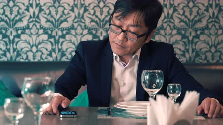 chafe : Asian man in suit businessman waiting in the cafe their food. Long waits for ordering. Nervous