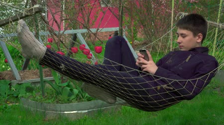 faház : 4K Portrait boy Playing Tablet in Hammock, the young man Face Use Smart Phone in Nature