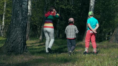 mamãe : Mother and two children walking in the woods during the summer (slow-mo) Stock Footage