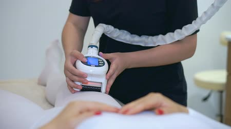 lipolysis : The girl beautician uses modern cosmetic equipment. Hardware laser therapy