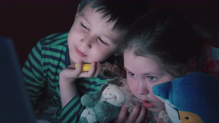 Brother and sister watching videos on the laptop lying on bed in the evening 4K