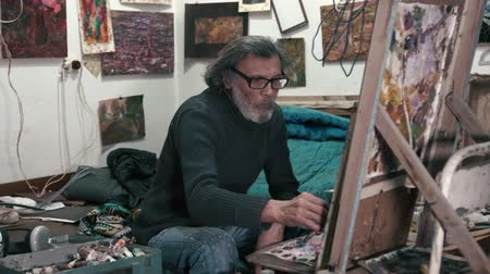 Old artist working on painting