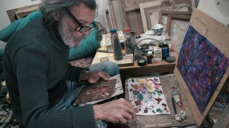 dab : The gray-haired artist mixes oil paints to paint (4K)