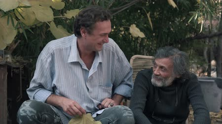 Middle-aged man and white-haired old man sitting outdoors and laughing 4K