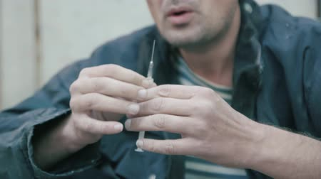 Man prepares a syringe for injection of drugs 4K