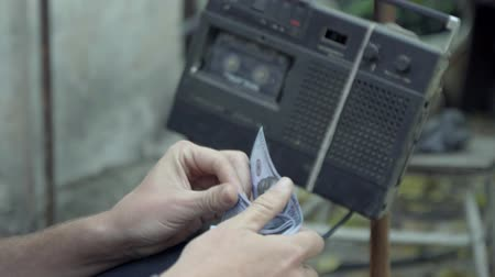 Homeless counts the dollars, on the background of vintage tape recorder 4K