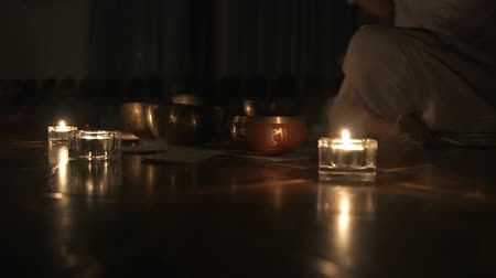 The Tibetan singing bowls. A woman plays music in the dark on singing bowls. Candlelight