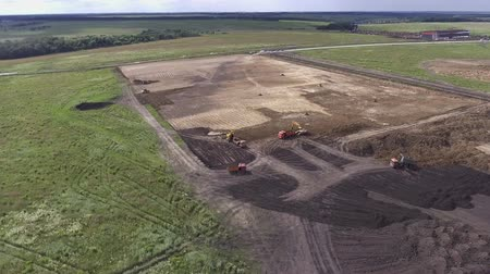 Aerial flight over earth moving machines and construction site. Flight over the field where the construction equipment
