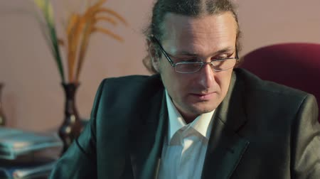 sobre : A man with glasses sitting in the office and working for a laptop. Close-up face only Stock Footage
