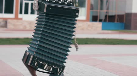 linked : The wanderer walks around the city and carries an accordion. Tied by ropes. Close-up