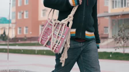 linked : Young male (hipster) walks and carries a musical drumbox synth. Tied by ropes. Close-up