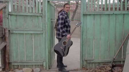 сценарий : A man leaves home alone with a guitar. The hairy man comes out of the gate of the old house.