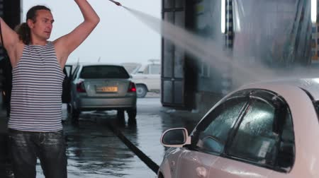 lavagem : Man washing his car with water spray from high pressure washer. Car wash self-service. Caucasian man.