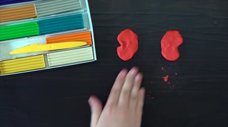plastelíny : Only hand. The view from the top. The child sculpts a figure (butterfly) with plasticine. Modern style. Speed up video