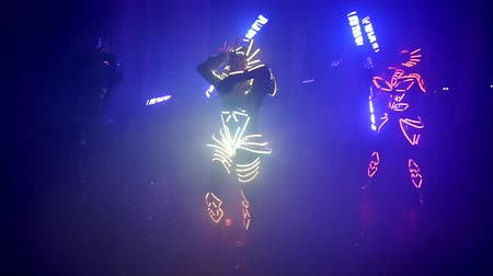 charged : Graceful girls and guys dancing in the glowing suits. Laser show, light show, LED show.