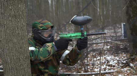pneumatic : A man in camouflage uniform and a protective mask shoots with an air gun. Paintball Game Stock Footage