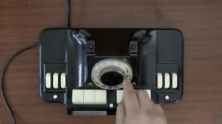 döner : Top view. Very old rotary phone. Hand spinning disk vintage telephone. Old communication technologies Stok Video