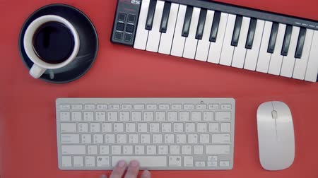 editor : Man hand playing a MIDI controller keyboard synthesizer. DJ musician creates a new track. Top view. Minimalism
