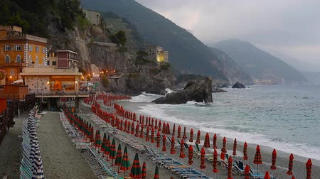 Лигурия : Umbrellas at the beach in Monterosso al Mare, Cinque Terre, Italy, rainy day, sea with waves and mountains in fog at horizon, evening lights
