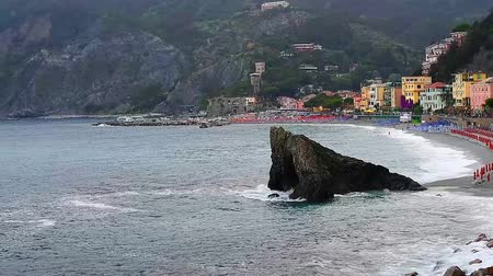 Лигурия : Dark sea and mountains with beach and buildings in Monterosso al Mare, Cinque Terre, Italy, rainy day, water crashing on rocks, top view