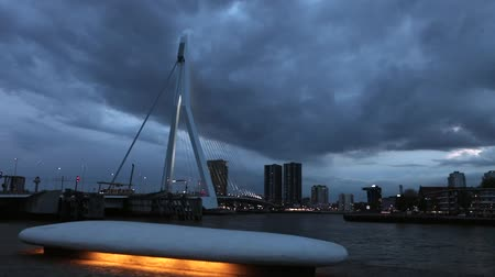 General view of Rotterdam city landscape and Erasmus bridge one of the most famous symbols of the city at twilight time with dramatic clouds. HD Footage.